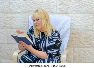 Beautiful middle age woman in outdoor patio reading a book sitting in armchair. Plus size lady holding an open book flicking through the pages. Happy mature woman with book outdoors.