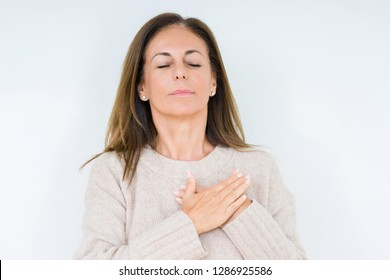 Beautiful middle age woman over isolated background smiling with hands on chest with closed eyes and grateful gesture on face. Health concept.