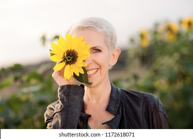 Beautiful middle age woman in a rural field scene outdoors standing between sunflowers, enjoying sunlight, summerly, autumn mood