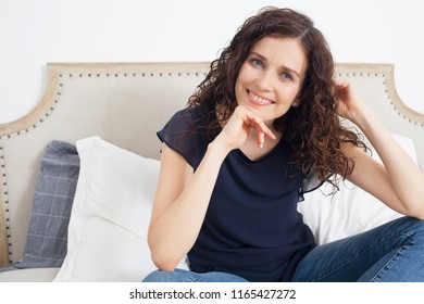 Beautiful middle age woman sitting relaxing on home bed in casual clothes, smiling looking at camera, in home interior. Nordic female leaning on hands in bedroom, indoors. Clean stylish lifestyle.