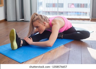 Beautiful middle age woman stretching and exercising on mat at her home. Fitness and health concept.