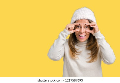 Beautiful middle age woman wearing winter sweater and hat over isolated background Trying to open eyes with fingers, sleepy and tired for morning fatigue