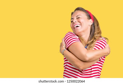 Beautiful middle age woman wearing casual stripes t-shirt over isolated background Hugging oneself happy and positive, smiling confident. Self love and self care
