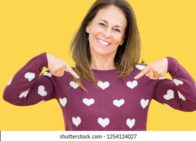 Beautiful middle age woman wearing hearts sweater over isolated background looking confident with smile on face, pointing oneself with fingers proud and happy.