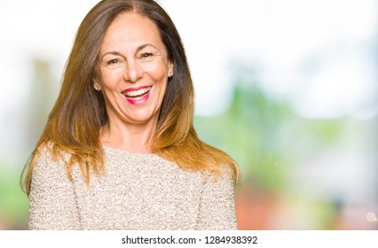 Beautiful middle age woman wearing fashion sweater happy face smiling with crossed arms looking at the camera. Positive person.