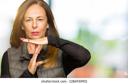 Beautiful middle age woman wearing winter vest Doing time out gesture with hands, frustrated and serious face