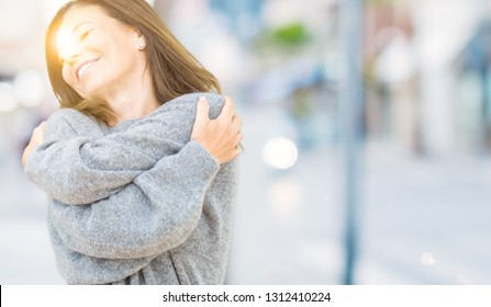 Beautiful middle age woman wearing winter sweater over isolated background Hugging oneself happy and positive, smiling confident. Self love and self care