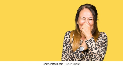 Beautiful middle age woman wearing leopard animal print dress smelling something stinky and disgusting, intolerable smell, holding breath with fingers on nose. Bad smells concept.