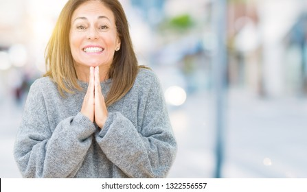 Beautiful middle age woman wearing winter sweater over isolated background praying with hands together asking for forgiveness smiling confident.