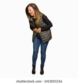 Beautiful middle age woman wearing winter vest with hand on stomach because nausea, painful disease feeling unwell. Ache concept.