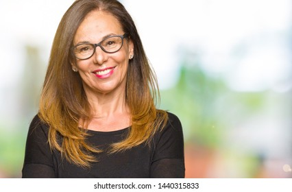 Beautiful middle age woman wearing glasses happy face smiling with crossed arms looking at the camera. Positive person.