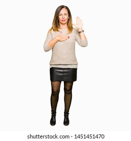 Beautiful middle age woman wearing fashion sweater Swearing with hand on chest and open palm, making a loyalty promise oath