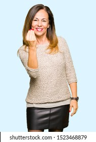 Beautiful middle age woman wearing fashion sweater Doing Italian gesture with hand and fingers confident expression