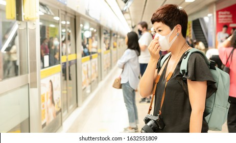 Beautiful middle aged Asian female traveller cover mouth and cough, wear medical face mask to protect from infection of viruses, pandemic, outbreak and epidemic of disease in crowded underground train