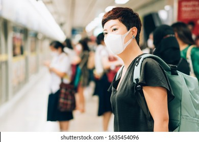 Beautiful middle aged Asian female traveller with worried look, wear medical face mask to protect from infection of viruses, pandemic, outbreak and epidemic of disease in crowded underground train
