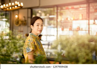 Beautiful middle aged Asian woman looking at camera in coffee shop
