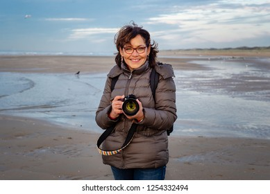 Beautiful, middle aged Brazilian woman with glasses on the beach, holding a camera. She looks at the photographers camera and and laughs and smiles. Cold, blue, beautiful day in the Netherlands.