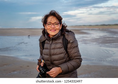 Beautiful, middle aged Brazilian woman with glasses on the beach, holding a camera. She looks through the camera and takes pictures along the ocean. Cold, blue, beautiful day in the Netherlands.