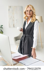 beautiful middle aged businesswoman in eyeglasses holding cup of coffee and looking at camera