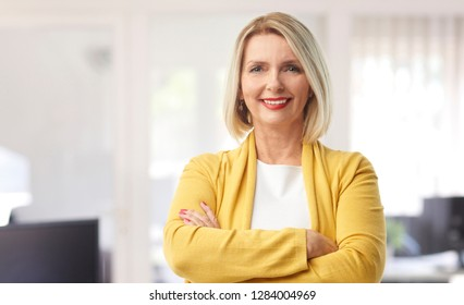 A beautiful middle aged financial assistant businesswoman wearing casual clothes and smiling to you while standing with arms crossed at the office.