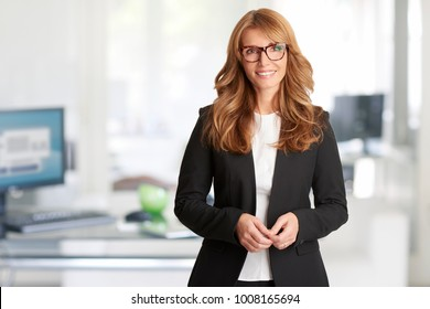 A beautiful middle aged financial businesswoman looking at camera and smiling while standing in the office after business meeting.