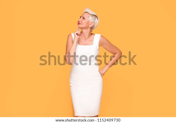 Beautiful middle aged lady emotionally posing on yellow studio background.