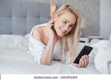 Beautiful middle aged, smiling blond woman lying in white bed and using a smartphone in her bedroom.