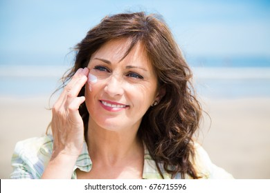 Beautiful middle aged woman applying sunscreen lotion on face on the beach