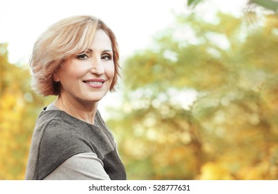 Beautiful middle aged woman in autumn park
