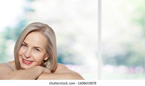 Beautiful middle aged woman fase close up on nature background. Happyness face, cheerful girl.