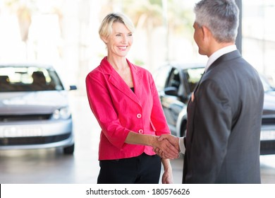 beautiful middle aged woman handshaking with car dealer