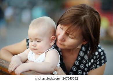 Beautiful middle aged woman and her adorable little grandson at the summer park