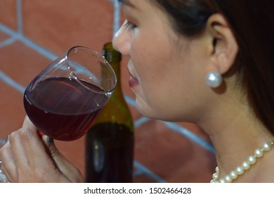 beautiful middle aged woman holding wine glass close to her lips