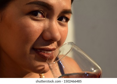 beautiful middle aged woman holding wine glass close to her lips, looking. close up