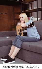 beautiful middle aged woman leaning at guitar and looking away at home