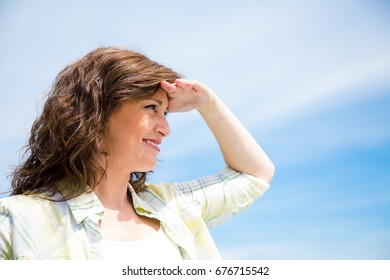 Beautiful middle aged woman making a visor with the hand against a blue sky