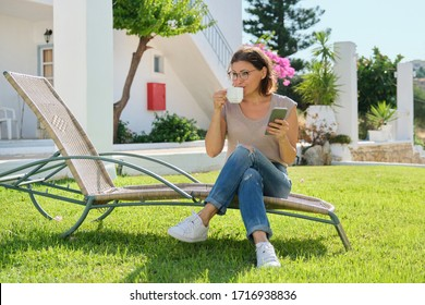 Beautiful middle aged woman resting reading drinking coffee chatting. Female sitting on garden lounger on lawn near house. Lifestyle, leisure, technology, beauty of mature people