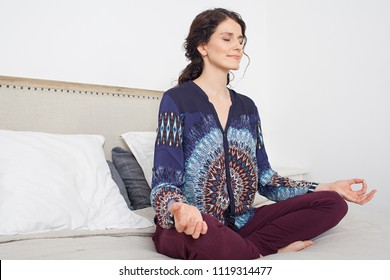 Beautiful middle aged woman sitting on bed doing yoga during morning, home bedroom interior space. Healthy female meditating, mind training, wellness mindful sport, indoors. Recreation lifestyle.