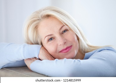 Beautiful middle aged woman smiling friendly and looking in camera in living room. Woman's face closeup. Realistic images without retouching with their own imperfections. Selective focus.
