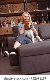 beautiful middle aged woman smiling at camera while sitting on sofa with dog