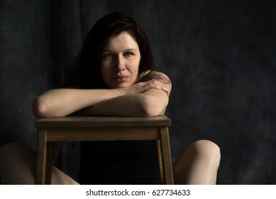 Beautiful middle aged woman with a tattoo, with chin on her elbows. Studio shoot on the black background.
