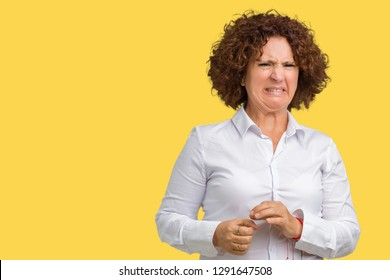 Beautiful middle ager senior businees woman over isolated background disgusted expression, displeased and fearful doing disgust face because aversion reaction. With hands raised. Annoying concept.