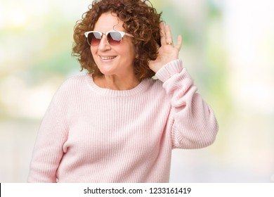 Beautiful middle ager senior woman wearing pink sweater and sunglasses over isolated background smiling with hand over ear listening an hearing to rumor or gossip. Deafness concept.