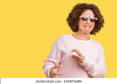 Beautiful middle ager senior woman wearing pink sweater and sunglasses over isolated background disgusted expression, displeased and fearful doing disgust face because aversion reaction