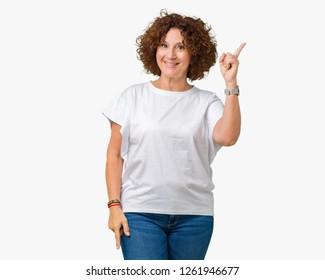 Beautiful middle ager senior woman wearing white t-shirt over isolated background cheerful with a smile of face pointing with hand and finger up to the side with happy and natural expression on face