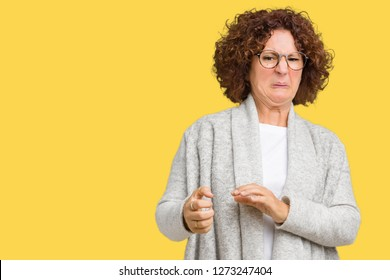 Beautiful middle ager senior woman wearing jacket and glasses over isolated background disgusted expression, displeased and fearful doing disgust face because aversion reaction. With hands raised