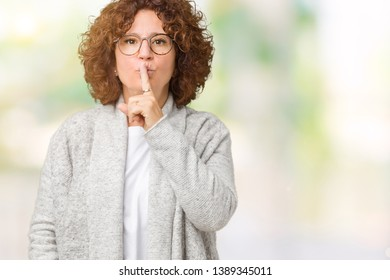 Beautiful middle ager senior woman wearing jacket and glasses over isolated background asking to be quiet with finger on lips. Silence and secret concept.