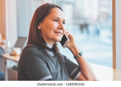 Beautiful middle-aged adult woman smiling and talking on the phone in cafe