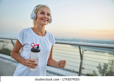 Beautiful middle-aged athletic woman with a happy smile running on a footbridge in the evening