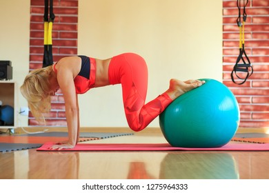 Beautiful middle-aged blonde woman in bright orange tracksuit does exercises with a green fitball in a fitness center.